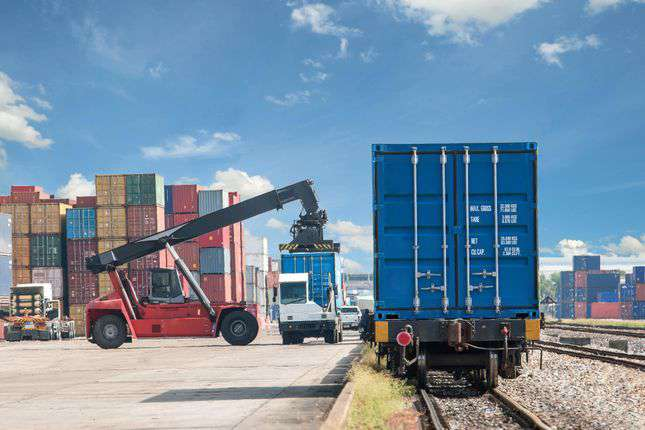 crane loading freight containers on a railcar